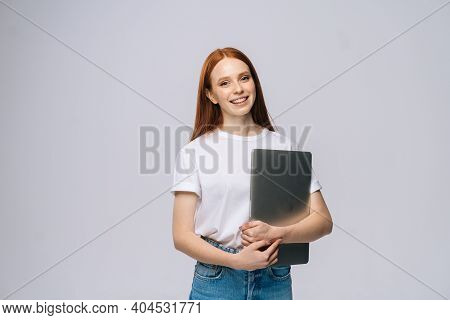 Cheerful Young Woman Student Holding Laptop Computer And Looking At Camera On Isolated Gray Backgrou