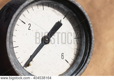Old Rusty Round Industrial Pressure Gauge With Numbers On A White Dial.