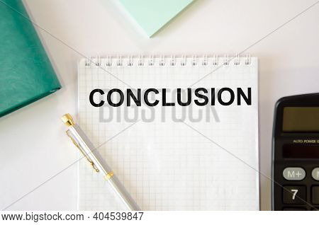 The Word Conclusion Is Written On A White Notepad Which Lies On A White Background Near The Calculat