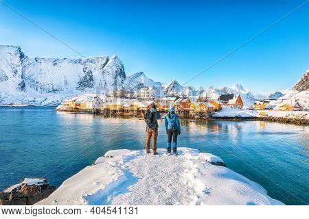 Сouple Of Tourists Admire The View Of The Sakrisoy Village And Snowy Mountaines On Background. Popul