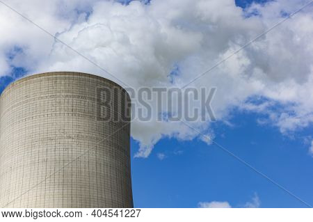 The Image Shows A Smoking Industrial Tower With Blue Sky