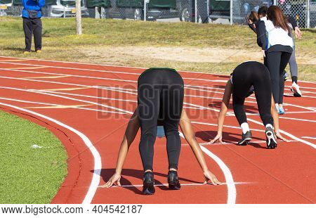 Rear View Of Female Sprinter Runners In The Set Position On On Outdoor Track During A High School Tr