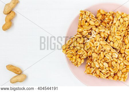 Traditional Indian Peanut Chikki On Plate On White Background, Top View. Candied Peanut Brittle Piec
