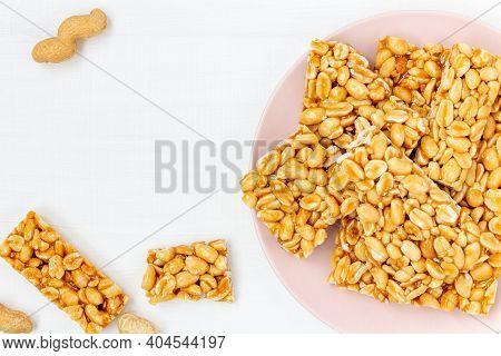 Sweet Peanut Kozinaki (gozinaki) On Dish On White Table, Flat Lay.  Peanut Brittle Candies On Pink P