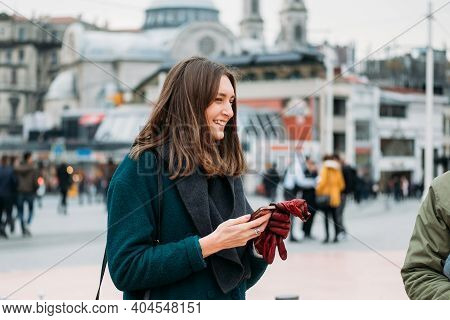 Turkey, Istanbul, December 14, 2018: Beautiful Girl In A Coat With A Smartphone On Taksim Square Smi