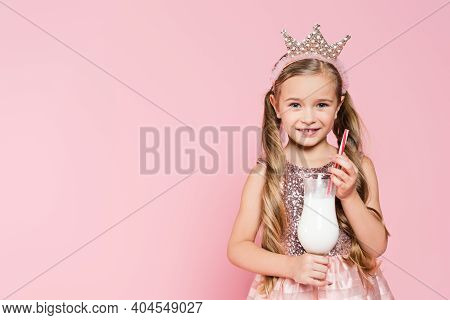 Happy Little Girl In Dress And Crown Holding Glass With Milkshake Isolated On Pink