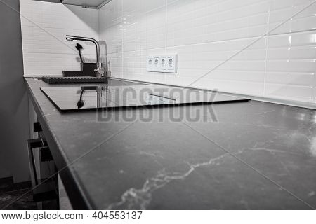 Modern White Kitchen With Apron. Black Countertop And Induction Touch Plate. In The Dim Light