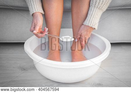 Woman Put Spoon Of Baking Soda In Bath With Hot Water For Her Feet. Homemade Bath Soak For Dry Feet