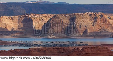 Red Sandstone Leads Into The Busy Wehweap Marina On Lake Powell Then To Pale Sandstone Cliffs Lit By