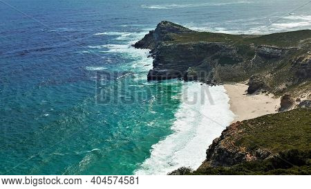 The Legendary Cape Of Good Hope. Rugged Rocky Coastline And Small Secluded Beach. The Turquoise Wave