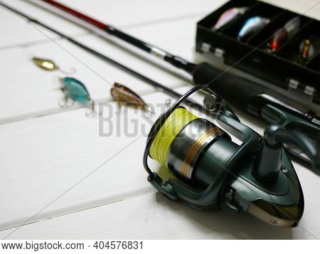 Fishing Tackles Lay On White Wooden Boards. Set Of Fishing Tackles. Close Up View On Spool, Rod, Wob