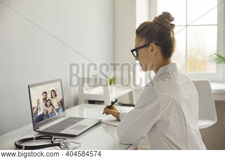 Young Woman Doctor Therapist In White Uniform Listening To Complaints Of Happy Family Online