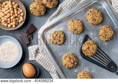 Horizontal composition of a baking tray with freshly baked chickpea cookies and dark chocolate chips, some ingredients and a turner