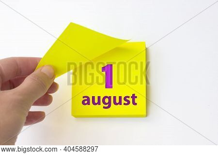 August 1st . Day 1 Of Month, Calendar Date. Hand Rips Off The Yellow Sheet Of The Calendar. Summer M