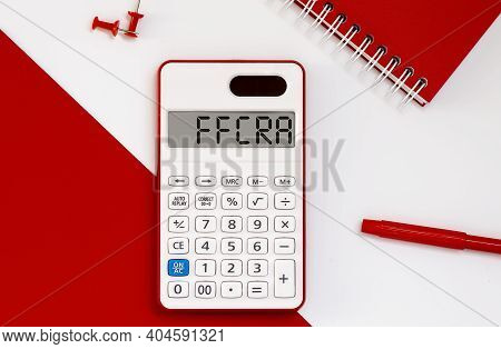 Calculator With The Word Ffcra On Display With Red Notepad And Office Tools