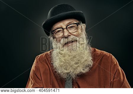 Portrait of an old-fashioned old man with a white beard in a bowler hat and spectacles. Old age. Black background.