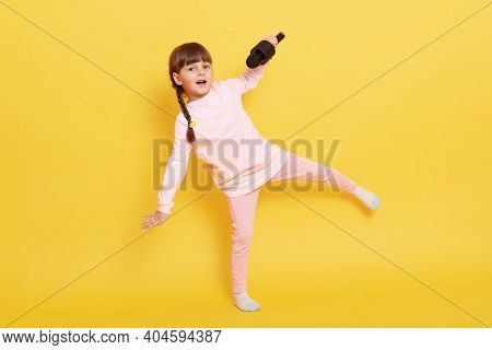 Happy Smiling Little Girl Jumping And Singing In Microphone, Small Vocalist Wearing Casual Clothing