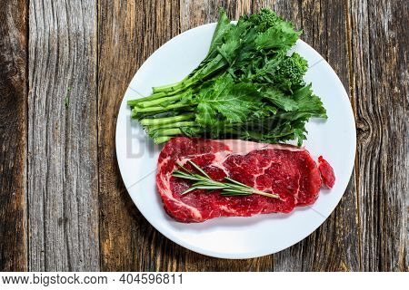 Uncooked boneless club steak onplate with rosemary and babe broccoli  on rustic wooden table from above