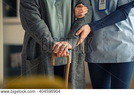 Close up hands of caregiver doctor helping old woman at clinic. Nurse holding a senior patient with walking stick. Elder woman using walking cane at nursing home with nurse holding hand for support.