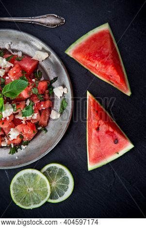 Fresh salad with water-melon, feta cheese, lime and mint, top view.