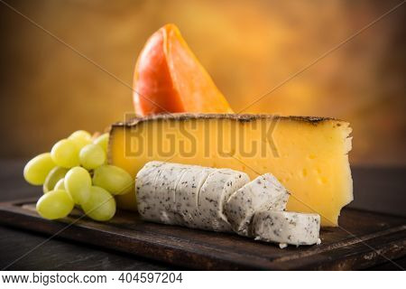 Set of different types of cheese on old wooden background, close up.