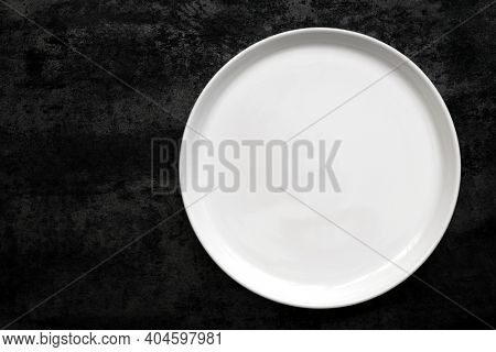 Empty white plate over black slate.  Top view, flat lay, with copy space.