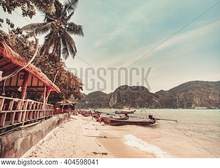 Thailand autumn beach pier: boats at ocean coast waterfront. Water transport at mountain asian island. Asia resort with resting people. Exotic nature in tropical fall soft tones in cinematic shot