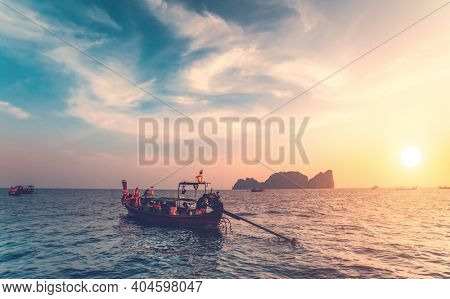 Thailand ocean boats cruise: people traveling on water transport at sun setting tones. Majestic sunset tourist vacation at waterfront. Mountain island silhouette at skyline under cloudy sky