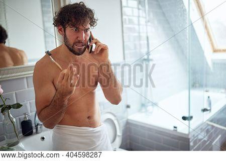 Topless man fighting while brushing teeth in the bathroom