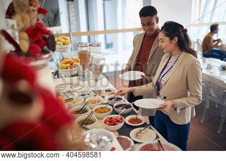 afro-american male and asian female having lunch break at business seminar