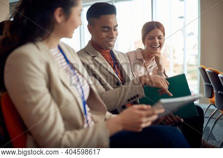 young afro-american male pointing with his pinkie finger detail in script at business conference to his asian female colleague, smiling
