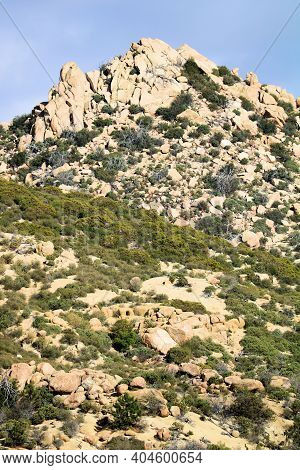 Large Rocks And Boulders Surrounded By Chaparral Plants On An Arid Hillside At The Mojave Desert In