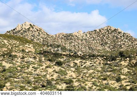 Rural Hills Covered With Large Rocks And Boulders On Arid Badlands Taken At The Mojave Desert In The