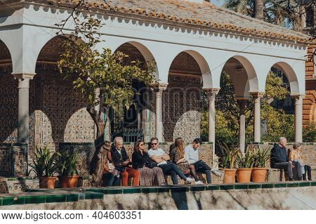 Seville, Spain - January 19, 2020: People Relaxing On Benches In The Garden Of The Ladies In Alcazar