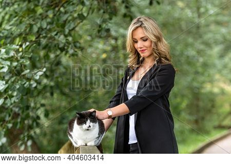 Young Beautiful Woman With Cat Standing Near Wooden Railings In Park