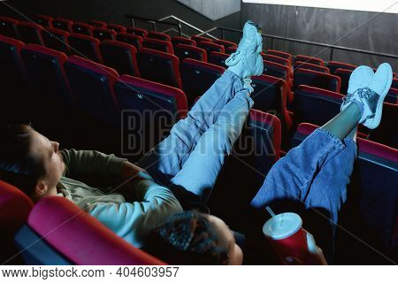 High Angle View Of Couple Of Friends In Casual Clothes Putting Their Feet On Seats While Watching A