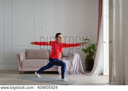 Middle Aged Woman Practices Yoga At Home. Archer Pose. Healthy Lifestyle Concept.