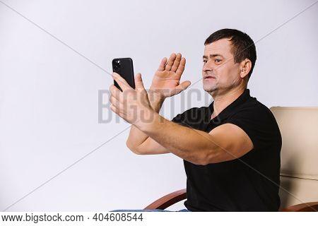 Non-verbal Greeting. Hard Of Hearing Senior Man Communicates Via Video On Modern Smartphone. White B