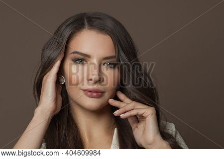 Beautiful Woman Face With Healthy Skin And Hair On Brown Background