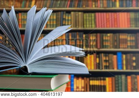 Book In Library With Old Open Textbook, Stack Piles Of Literature Text Archive On Reading Desk, And