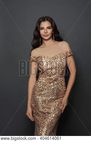 Glamorous Fashion Model Woman In Golden Evening Dress On Black Background