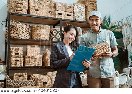 Asian Woman Holds The Clipboard And The Man Holds The Wicker Box While Checking Items
