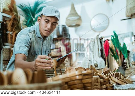 Man Holds A Craft Item And Clipboard While Checking Items Among Craft Items