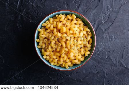 Blue Bowl With Cavatappi Uncooked Golden Wheat Curly Pasta On Textured Dark Black Background, Top Vi
