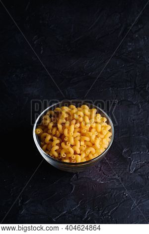 Glass Bowl With Cavatappi Uncooked Golden Wheat Curly Pasta On Textured Dark Black Background, Angle