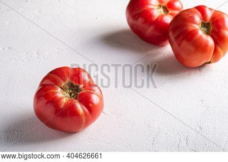 Three Pink Heirloom Tomato Vegetables, Fresh Red Ripe Tomatoes, Vegan Food, White Stone Concrete Bac