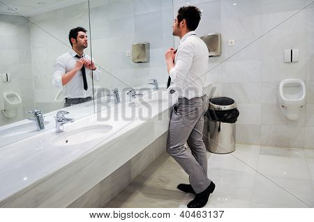 Man Getting Dressed In A Public Restroom With Mirror