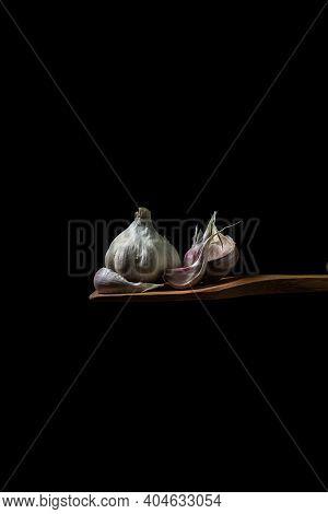 Garlic On A Black Background. Garlic Cloves Next To Whole Garlic. Garlic On A Wooden Spatula