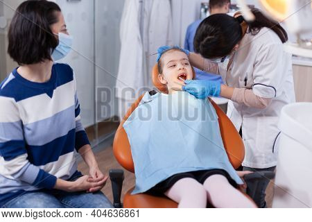 Stomatology Doctor Using Dental Mirror In The Course Of Little Girl Examination. Dentistry Specialis