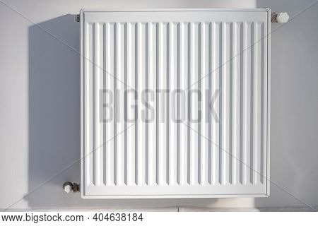 A Steel Panel Heating Radiator Is Placed On A White Wall.